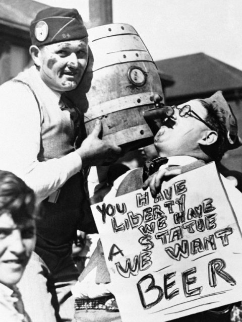 """A prohibition-thirsty American Legionnaire goes into action in Windsor, Canada August 17, 1954, where the beer flowed freely, during the 1931 Legion convention across the river and the border in Detroit, Mich. His sign reads: """"You have liberty – we have a state – we want Beer"""". Legion officials have decreed a """"safe and sane"""" convention this year, in Washington, D.C. (Photo by AP Photo)"""