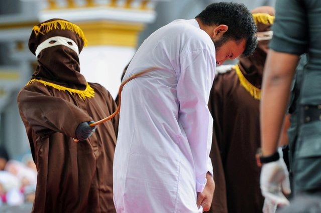 An Indonesian man (C), one of two to be publicly caned for having s*x, is caned in Banda Aceh on May 23, 2017. .The pair, aged 20 and 23, were found guilty of having broken sharia rules in conservative Aceh province – the only part of Indonesia that implements Islamic law – and sentenced to 85 strokes of the cane each. (Photo by Chaideer Mahyuddin/AFP Photo)