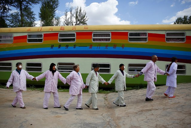 A nurse (R) leads cataract patients as they walk past a train which serves as a mobile hospital, in Ledu county, Qinghai province, China, July 23, 2015. The train, donated by people from Hong Kong and Macau, came to the county three months ago and has provided free medical treatment to over 900 local cataract patients, local media reported. (Photo by Simon Zo/Reuters)