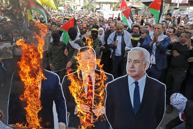 Palestinian protesters burn cardboard cutouts of US President Donald Trump, his State Secretary Mike Pompeo, and Israeli Prime Minister Benjamin Natanyahu, during a demonstration in the center of Nablus city in the occupied West Bank on November 26, 2019, against the US policy shift on Israeli settlements in Palestinian Territories. Pompeo announced last week that the United States no longer considers Israeli settlements in the West Bank and Israeli-annexed east Jerusalem illegal, a shift that came nearly two years after President Donald Trump overturned decades of policy by recognising the contested holy city of Jerusalem as Israel's capital, sparking Palestinian and Arab anger. (Photo by Jaafar Ashtiyeh/AFP Photo)
