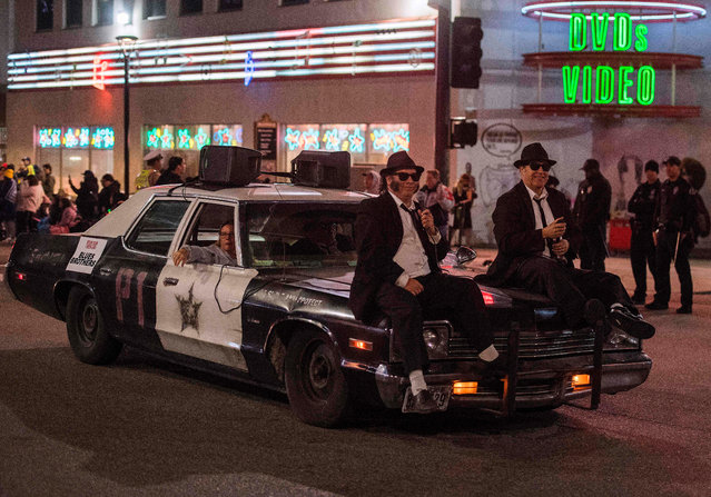"""A car from the """"Blues Brothers"""" movie is driven down Sunset Blvd during the 88th annual Hollywood Christmas Parade in Hollywood, California on December 1, 2019. (Photo by Mark Ralston/AFP Photo)"""