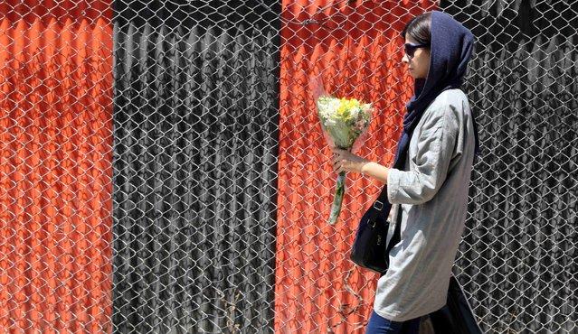 A woman walks on a sidewalk in northern Tehran, Iran, July 27, 2015. (Photo by Reuters/TIMA)