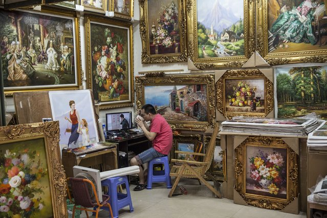 An artist eats his lunch at a gallery packed with still lifes and reproductions at the artist village on June 11, 2014 in Shenzhen, China. The Dafen Artist Village in Guangdong province, China, is home to thousands of artists who reproduce some of the world's most iconic paintings as well as create their own works. The village, on the outskirts of Shenzhen, is becoming a major center for original Chinese art. (Photo by Palani Mohan/Getty images)