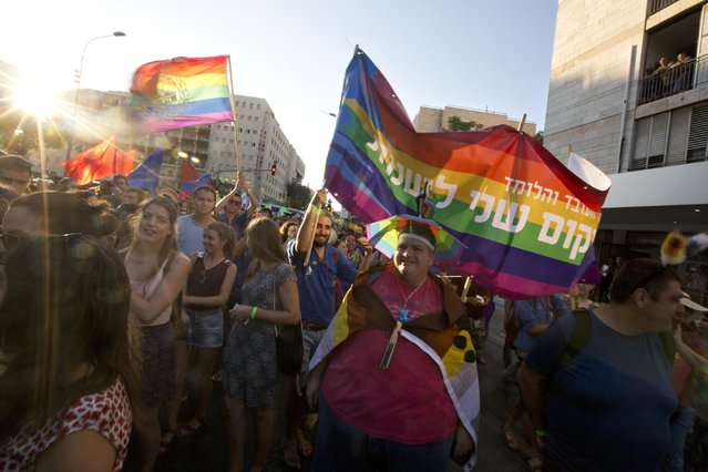 People carry flags during a Gay Pride parade before an ultra-Orthodox Jew stabbed several people with a knife in Jerusalem on Thursday, July 30, 2015. (Photo by Sebastian Scheiner/AP Photo)