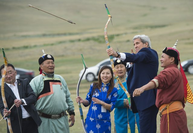 US Secretary of State John Kerry shoots a bow and arrow as he participates in a Naadam ceremony, a competition which traditionally includes horse racing, Mongolian wrestling and archery, in Ulan Bator, Mongolia on June 5, 2016. Kerry arrived in Mongolia on June 5, the latest senior US official to make the trip to the mineral-rich country neighboured by Russia and China. (Photo by Saul Loeb/AFP Photo)