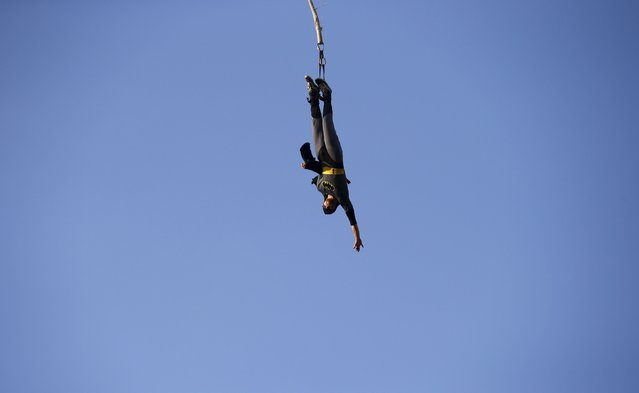 A reveler dressed as Batman bungee jumps during the 21st Woodstock Festival in Kostrzyn-upon-Odra, Poland July 31, 2015. (Photo by Kacper Pempel/Reuters)