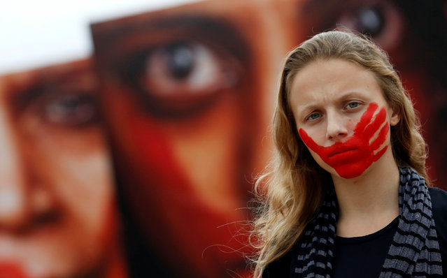 An activist poses for picture in front photos from Brazilian photographer Marcio Freitas, during a protest by non-governmental organization (NGO) Rio de Paz (Rio of Peace) against rape and violence against women on Copacabana beach in Rio de Janeiro, Brazil, June 6, 2016. (Photo by Sergio Moraes/Reuters)