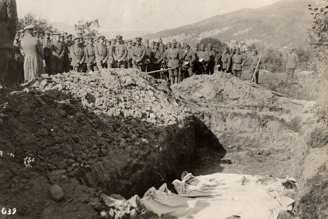 Austro-Hungarian soldiers stand in front of a mass grave on the Eastern Front in this 1915 handout picture. This picture is part of a previously unpublished set of World War One (WWI) images from a private collection. The pictures offer an unusual view of varied and contrasting aspects of the conflict, from high tech artillery to mobile pigeon lofts, and from officers partying in their headquarters to the grim reality of life and death in the trenches. The year 2014 marks the centenary of the start of the war. (Photo by Reuters/Archive of Modern Conflict London)