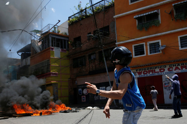 Venezuelan protesters burn tires and clash with riot police during a protest over food shortage and against Venezuelan President Nicolas Maduro's government in Caracas, Venezuela June 10, 2016. (Photo by Carlos Garcia Rawlins/Reuters)