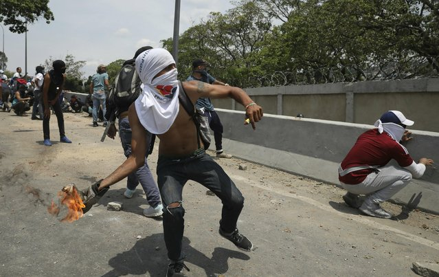 An anti-government protester launches a molotov cocktail at National Guard forces outside La Carlota airbase during clashes between the two sides in Caracas, Venezuela, Wednesday, May 1, 2019. (Photo by Rodrigo Abd/AP Photo)