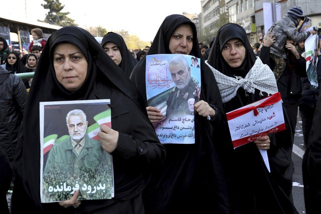 Mourners holding posters of Iranian Gen. Qassem Soleimani attend a funeral ceremony for him and his comrades, who were killed in Iraq in a U.S. drone strike on Friday, at the Enqelab-e-Eslami (Islamic Revolution) Square in Tehran, Iran, Monday, January 6, 2020. The processions mark the first time Iran honored a single man with a multi-city ceremony. Not even Ayatollah Ruhollah Khomeini, who founded the Islamic Republic, received such a processional with his death in 1989. Soleimani on Monday will lie in state at Tehran's famed Musalla mosque as the revolutionary leader did before him. (Photo by Ebrahim Noroozi/AP Photo)