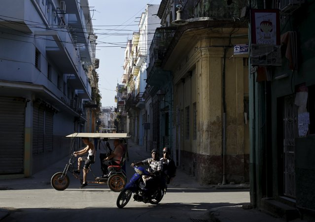 People are seen riding a motorcycle as a trishaw driver ferries passengers in Havana July 20, 2015. (Photo by Enrique De La Osa/Reuters)