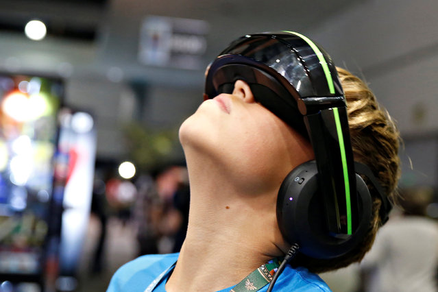 A boy samples the Vuzix iWear video headphones, which are billed as the equivalent to a 125 inch screen viewed from 10 feet, at the E3 Electronic Expo in Los Angeles, California, U.S. June 14, 2016. (Photo by Lucy Nicholson/Reuters)