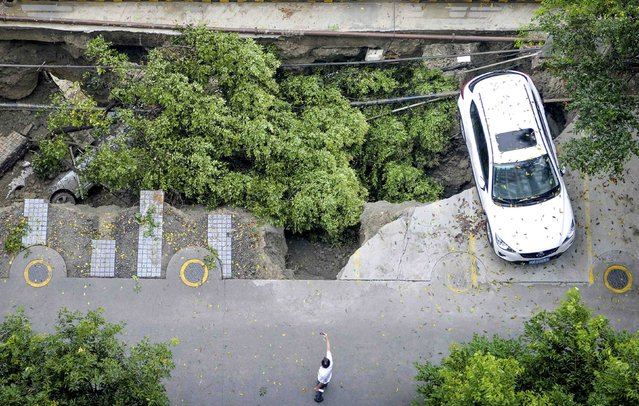 A man takes pictures of a sunken open-air parking lot after heavy rainfall hit Chengdu, Sichuan province, July 9, 2014. (Photo by Reuters/China Daily)