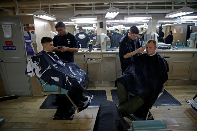 US Navy sailors gets a hair cut at the barber shop on board of the USS Harry S. Truman aircraft carrier in the eastern Mediterranean Sea, June 14, 2016. (Photo by Baz Ratner/Reuters)