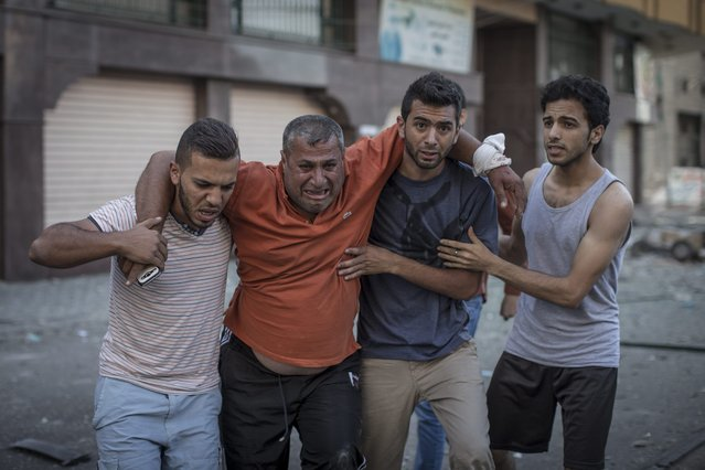 Palestinian men help a local journalist who got injured during an Israeli airstrike on an office building hosting several media outlets in Gaza City, 18 July 2014. (Photo by Oliver Weiken/EPA)