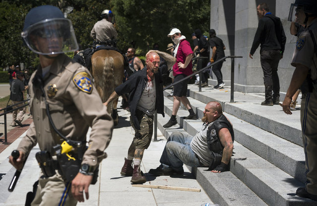 A wounded man stands by another wounded man sitting on the steps of the California state Capitol after members of right-wing extremists groups holding a rally outside the state Capitol building clashed with counter-protesters in Sacramento, Calif., Sunday, June 26, 2016. Several people were stabbed Sunday when counter-protesters clashed with members of right-wing extremists groups that planned to hold a rally outside the Capitol building, authorities said. (Photo by Paul Kitagaki Jr./The Sacramento Bee via AP Photo)