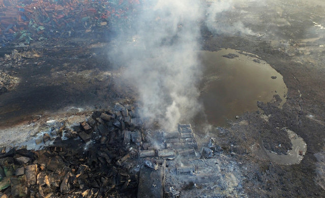 Smoke rises from debris near a crater that was at the center of a series of explosions in northeastern China's Tianjin municipality Saturday, August 15, 2015, as seen from an aerial view. New explosions and fires rocked the Chinese port city of Tianjin on Saturday, as one survivor was pulled out and authorities ordered evacuations to clean up chemical contamination more than two days after a fire and a series of blasts set off the disaster. (Photo by Chinatopix Via AP Photo)