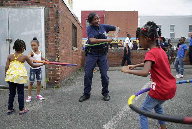 Baltimore Police Officer Chantell English, center, and young girls play with hula hoops in the Penn North neighborhood of Baltimore, Thursday, June 23, 2016, near the site of unrest following the funeral of Freddie Gray. Officer Caesar Goodson, one of six Baltimore city police officers charged in connection to the death of Gray, was acquitted of all charges in his trial Thursday. (Photo by Patrick Semansky/AP Photo)