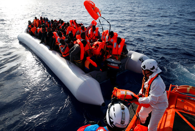 Migrants in a dinghy reach out for life jackets thrown to them by rescuers of the Migrant Offshore Aid Station (MOAS) some 20 nautical miles off the coast of Libya, June 23, 2016. (Photo by Darrin Zammit Lupi/Reuters)