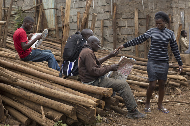 Kenyans read newspapers in the Kibera slum in Nairobi, Kenya, Monday August 7, 2017. (Photo by Jerome Delay/AP Photo)