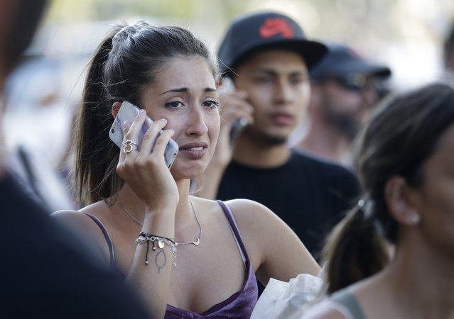 People speak on their phones as they stand on a street in Barcelona, Spain, Thursday, August 17, 2017. Police in the northern Spanish city of Barcelona say a white van has jumped the sidewalk in the city's historic Las Ramblas district, injuring several people. (Photo by Manu Fernandez/AP Photo)