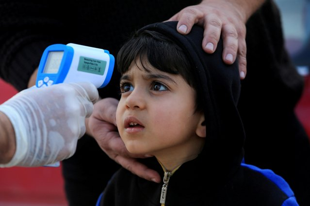 A member of the medical team checks the temperature of a child, following the coronavirus outbreak, at a checkpoint on the outskirts of Duhok, Iraq on March 2, 2020. (Photo by Ari Jalal/Reuters)