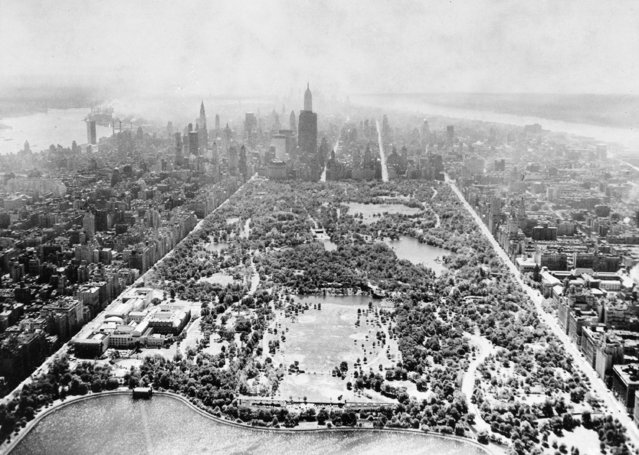This aerial view shows two-thirds of Central Park's 40 acres, looking south toward the tip of Manhattan, on August 26, 1957.  In the foreground is part of the billion-gallon reservoir, and the open space above contains six baseball diamonds. At left along Fifth Ave., is the Metropolitan Museum of Art. The tall skyscraper in the center is the Empire State Building. (Photo by AP Photo)