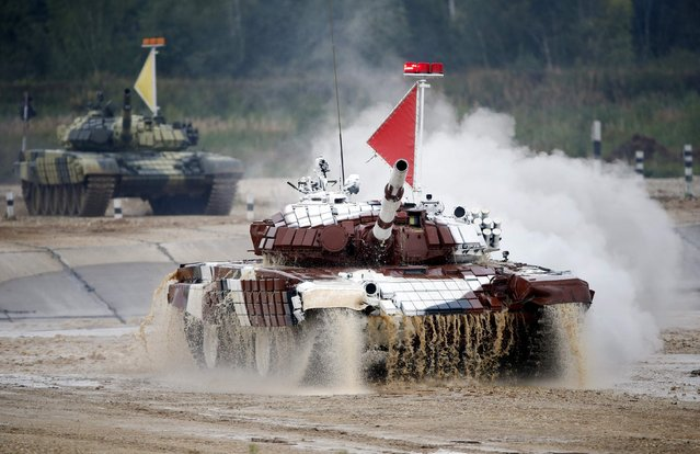 Tanks drive through the course of the Tank Biathlon world championship in Alabino outside Moscow August 16, 2014. The tank competition, where teams compete in tests of driving and shooting, for the first time brought together crews from 12 countries: Angola, Armenia, Belarus, Venezuela, India, Kazakhstan, Kyrgyzstan, China, Kuwait, Mongolia, Russia and Serbia, local media reported. (Photo by Maxim Zmeyev/Reuters)