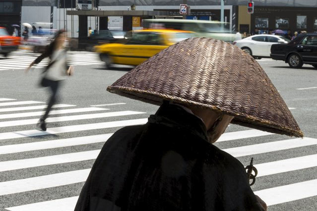 A Buddhist monk collects donations as a woman rushes over a pedestrian crossing in the Ginza district of Tokyo, July 27, 2015. (Photo by Thomas Peter/Reuters)