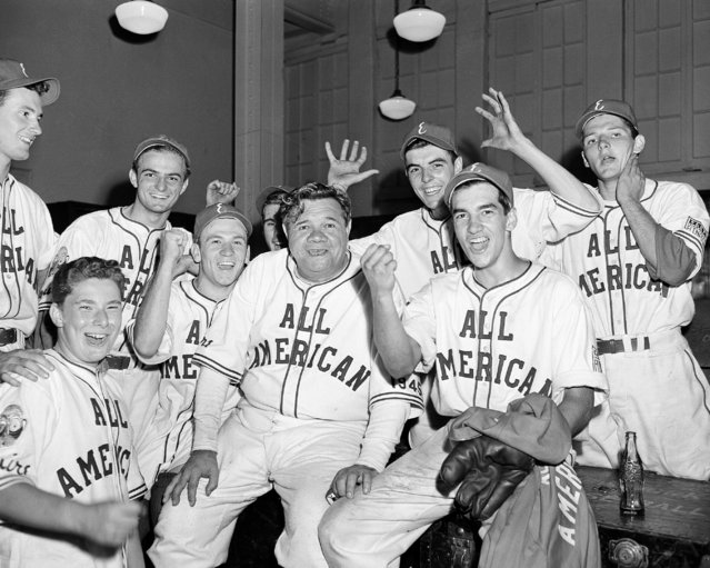 Yankees' legend Babe Ruth, center, is seen with some of his players on the All-American Boys East team as they cheer their 5-4 victory over the All-American West team in the second annual Esquire All-American baseball game at the Polo Grounds in New York, August 28, 1945. (Photo by Harry Harris/AP Photo)