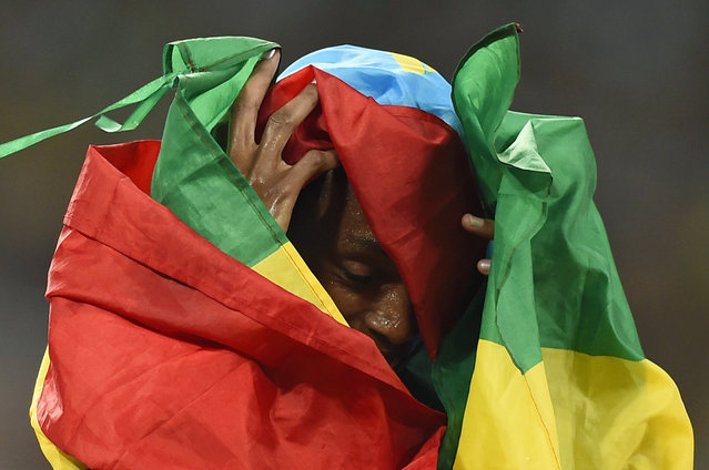 Almaz Ayana of Ethiopia gets tangled up in her national flag after winning the women's 5000 metres final at the 15th IAAF Championships at the National Stadium in Beijing, China August 30, 2015. (Photo by Dylan Martinez/Reuters)
