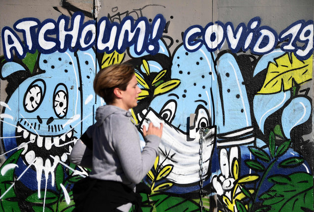 """A jogger passes by a mural with a message reading """"Achoo Covid-10"""" in the street on April 1, 2020, in Paris, on the sixteenth day of a lockdown in France aimed at curbing the spread of the COVID-19 (novel coronavirus). (Photo by Franck Fife/AFP Photo)"""