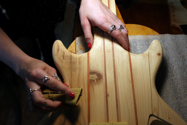 Cindy Hulej, an apprentice who works with Rick Kelly at Carmine Street Guitars, sands a guitar at Kelly's shop in New York City, U.S., July 21, 2016. (Photo by Joe Penney/Reuters)