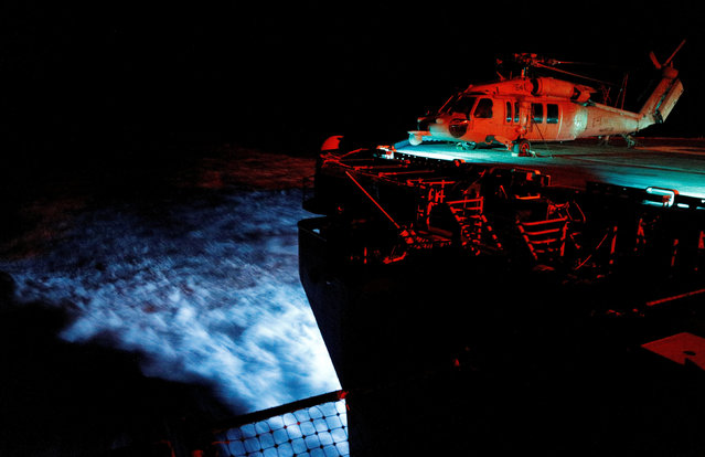 A Navy MH-60S Seahawk helicopter is illuminated by deck lights while the USS Kearsarge's aft is lit by blue trailing lights as the vessel motors at top speed towards islands impacted by Hurricane Maria, in the Caribbean Sea late September 20, 2017. (Photo by Jonathan Drake/Reuters)