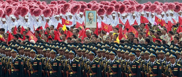Portrait of late Vietnamese revolutionary leader Ho Chi Minh is seen among soldiers during a parade marking their 70th National Day at Ba Dinh square in Hanoi, Vietnam September 2, 2015. (Photo by Reuters/Kham)