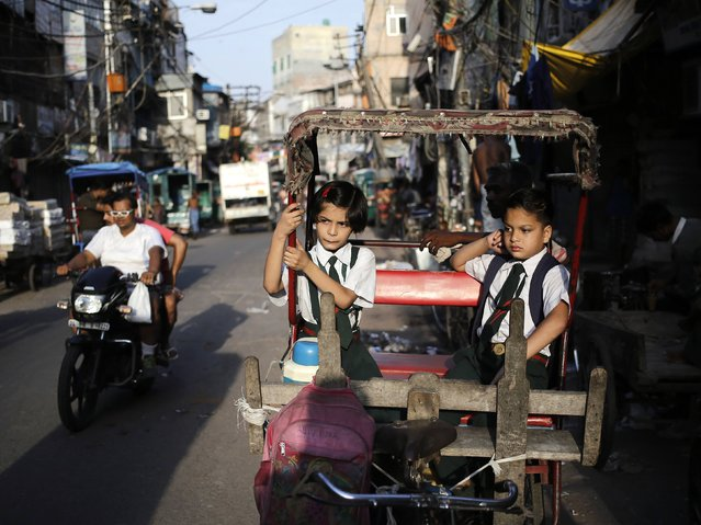 School children sit in a cycle rickshaw as they wait for the rickshaw-puller during the morning in the old quarters of Delhi August 27, 2014. (Photo by Anindito Mukherjee/Reuters)