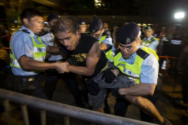 A pro-democracy activist is detained by the police during a confrontation outside the hotel where China's National People's Congress (NPC) Standing Committee Deputy General Secretary Li Fei is staying, in Hong Kong September 1, 2014. NPC Standing Committee set the stage for a political showdown on Sunday when it rejected democrats' demands for the right to freely choose Hong Kong's next leader in 2017, leading scores of protesters to take to the streets. (Photo by Tyrone Siu/Reuters)
