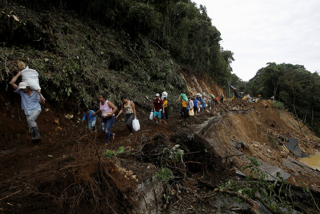 People traveling by bus for two days and were trapped between landslides walks in an area of a highway collapsed by Storm Nate in Casa Mata, Costa Rica October 6, 2017. (Photo by Juan Carlos Ulate/Reuters)
