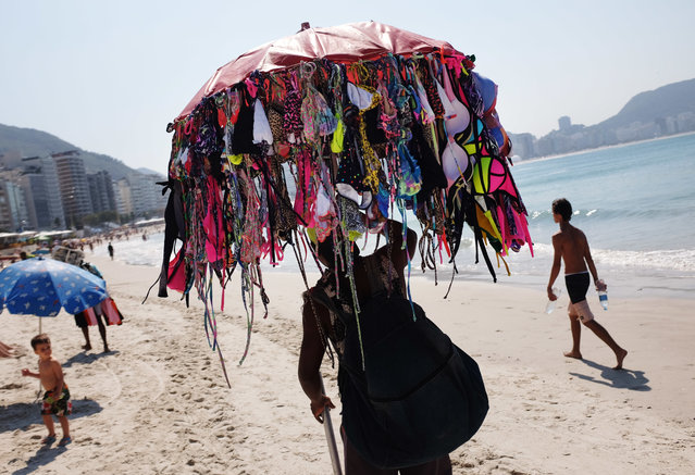 A vendor sells bikinis along Copacabana Beach ahead of the upcoming 2016 Summer Olympics in Rio de Janeiro, Brazil, Tuesday, August 2, 2016. The iconic Copacabana beach will be the starting point for the road cycling race, marathon swimming and triathlon competitions during the Olympics. (Photo by David Goldman/AP Photo)