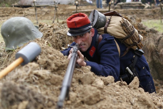 A local resident portraying a French WWI soldier attends the re-enactment of the First Battle of the Marne, which took place a century ago, at Chauconin-Neufmontiers, Eastern Paris September 6, 2014. Dozens of volunteers dressed in French and German military uniforms recreated the battle from two trenches dug out by local residents to mark the 100th anniversary of the start of the First World War (WWI). Picture taken September 6, 2014. (Photo by Charles Platiau/Reuters)