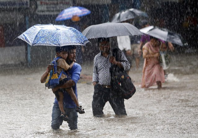 A man holds up a child as they walk though a water logged street during heavy rain in Mumbai, India, Friday, August 5, 2016. Trains and flights were reportedly delayed after severe rain lashed the city. (Photo by Rajanish Kakade/AP Photo)