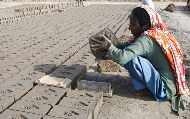 A woman works at a kiln to earn money for her family, during a government-imposed nationwide lockdown to help contain the spread of the coronavirus, in Lahore, Pakistan, Wednesday, April 15, 2020. (Photo by K.M. Chaudhry/AP Photo)