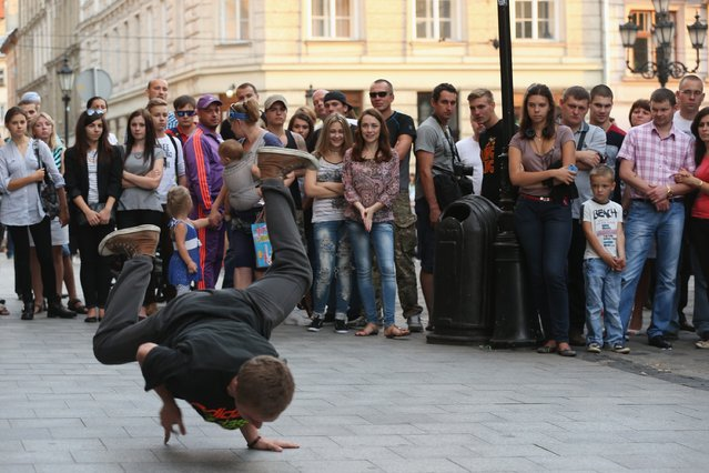 People watch a break dancer peform on a Sunday afternoon in the city center on Rynok Square on September 14, 2014 in Lviv, Ukraine. Hundreds of miles away sporadic fighting between pro-Russian separatists and the Ukrainian army in eastern Ukraine is continuing and many people doubt the current ceasefire overtures will lead to an end to the war. (Photo by Sean Gallup/Getty Images)