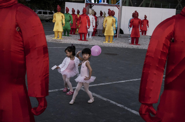 Chinese girls dressed in ballet costume pose for theif parents as theh take a picture in front of statues replicating China's famous Terracotta Warriors at an exhibtion on September 3, 2014 in Beijing, China. (Photo by Kevin Frayer/Getty Images)