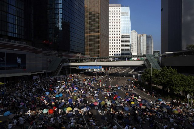 Protesters block the main road to the financial Central district (background) in Hong Kong September 29, 2014. Riot police advanced on Hong Kong democracy protesters in the early hours of Monday, firing volleys of tear gas after launching a baton-charge in the worst unrest there since China took back control of the former British colony two decades ago. (Photo by Bobby Yip/Reuters)