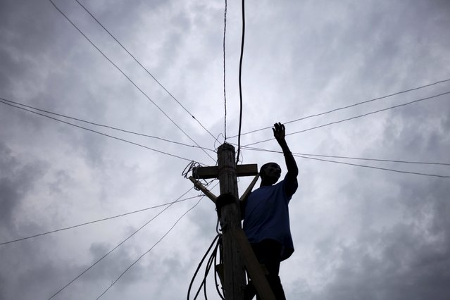 A man sets wires to provide electricity to temporary houses at a camp for displaced people in Port-au-Prince, Haiti March 6, 2016. (Photo by Andres Martinez Casares/Reuters)