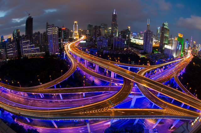 This long exposure picture shows vehicles on roads during rush hour on the eve of the National Day holidays in Shanghai on September 30, 2014. According to local media, police checkpoints will be set up at highways, elevated roads and business hubs to tackle drunk driving during the National Day holiday. (Photo by Johannes Eisele/AFP Photo)