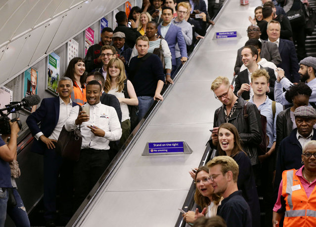 Mayor of London Sadiq Khan (left) travels down an escalator with members of the public at Brixton Underground station, during the launch of London's Night Tube August 20, 2016. (Photo by Yui Mok/Reuters/PA Wire)