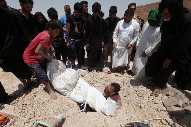 """Men bury a body at the Wadi al-Salam cemetery, Arabic for """"Peace Valley"""", in Najaf, south of Baghdad, Iraq July 27, 2016. (Photo by Alaa Al-Marjani/Reuters)"""